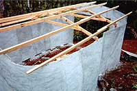 [rear quarter view of partially completed roof framing]